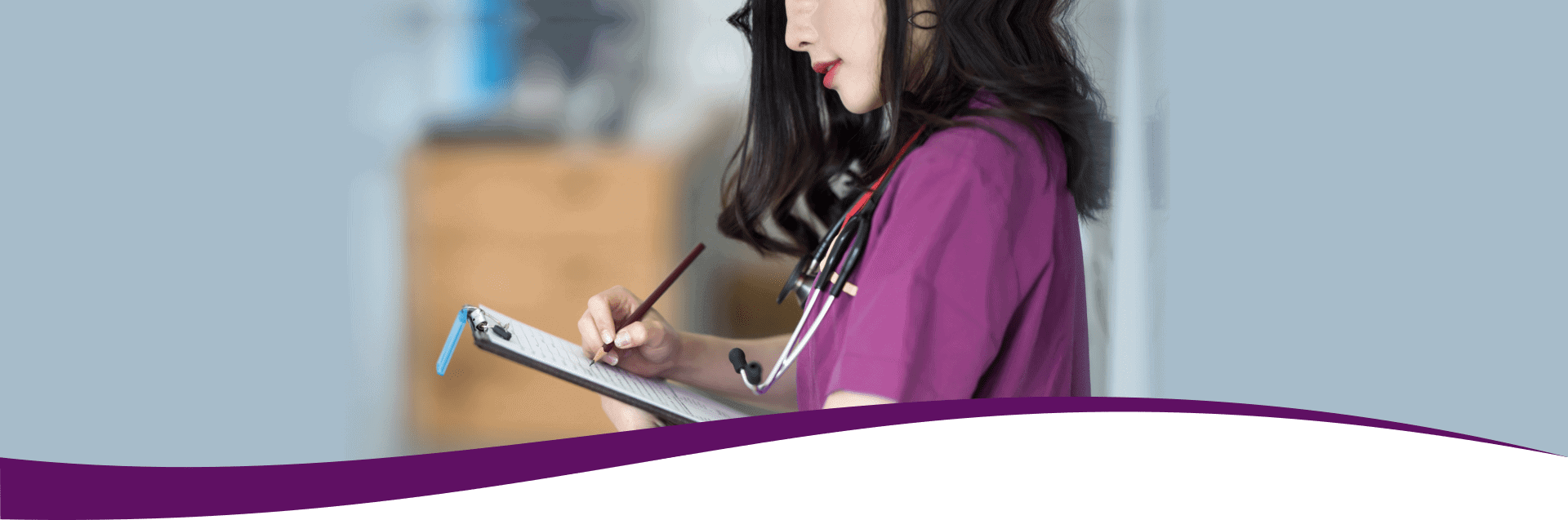 nurse wearing purple uniform standing besides the patient room while checking medical chart